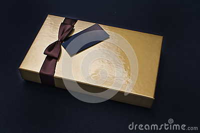 Golden chocolate box closed with black label Stock Photo