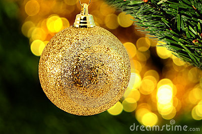 Golden christmas bauble with a leaf of evergreen