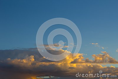 Golden clouds bathed by the sunset, in a beautiful blue sky Stock Photo