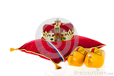 Golden crown on velvet pillow with wooden shoes