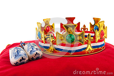 Golden crown on velvet pillow with Dutch wooden shoes