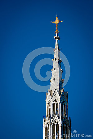 Golden Crucifix Atop Tall Church Steeple