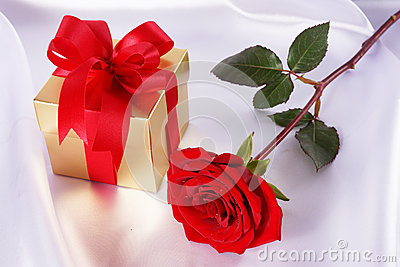 Golden gift box and red roses on white satin background