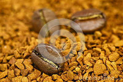 Golden ground coffee background with coffee beans