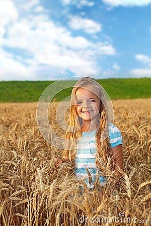 Golden hair girl on wheat field