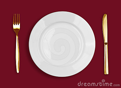 Golden knife, fork and white plate on red