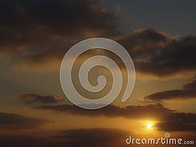 Golden light sunset view of a cloudy sky, sun hiding near yellow orange dark clouds Stock Photo