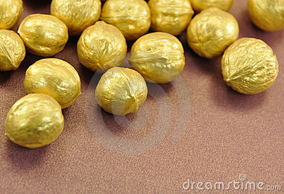 Golden Nuts on Brown Background