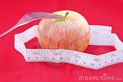 Golden-red apple with a meter and a fork on red