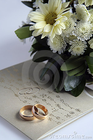 Golden rings, invitation and flowers