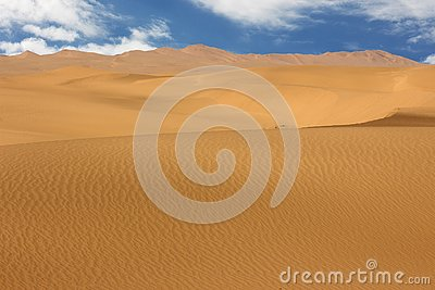 Golden sand dune and white clouds on a sunny day Stock Photo