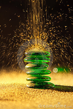 Golden sand falling on balancing green stones