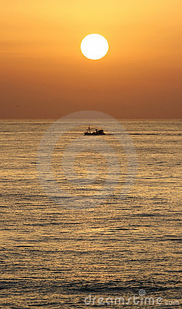 Golden sunrise in marbella, southern Spain with ocean and boat