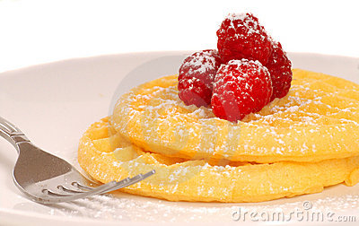 Golden waffles with raspberries and powdered sugar