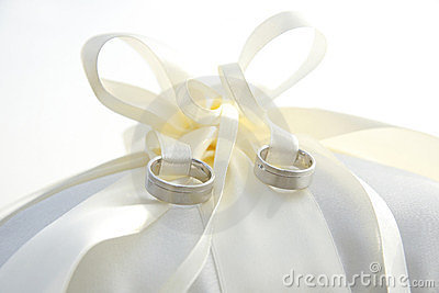Golden wedding rings laying on ring pillow