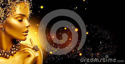Golden woman. Beauty fashion model girl with golden make up, hair and jewellery on black background Stock Photo