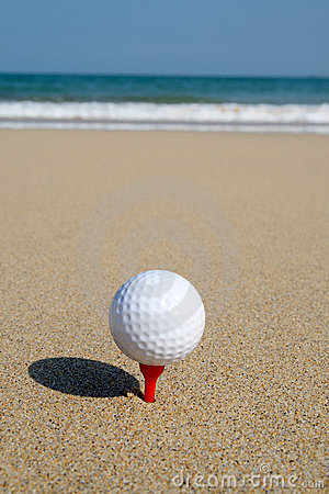 A golf ball on the beach.