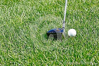 Golf ball behind driver at driving range, plenty o