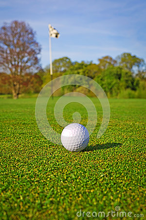 Golf ball on the course with flag