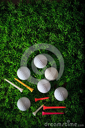 Golf ball driver and tee on green grass field