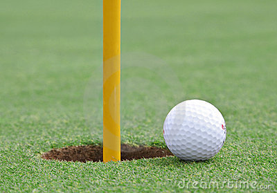 Golf ball on the edge of the cup