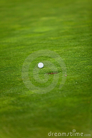 Golf ball going into a hole