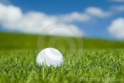 Golf ball on green fairway