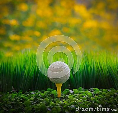 Golf ball on green grass field and yellow blur bac