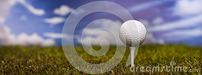 Golf ball on green grass over a blue sky