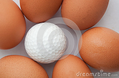 Golf ball and group of fresh eggs
