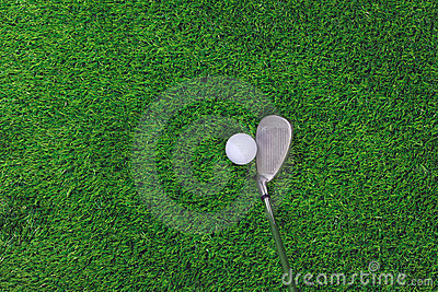 Golf ball and iron club on grass
