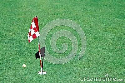 Golf ball near hole and flag