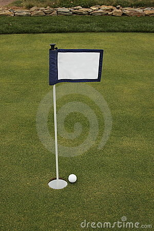 Golf ball near hole near putting green flag