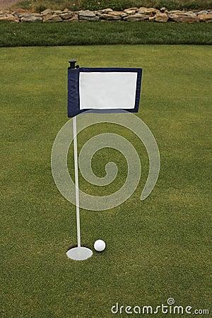 Golf ball near hole near putting green flag