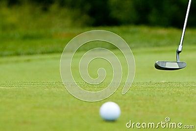 Golf ball and putter near green