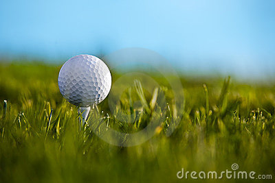 Golf ball sitting on tee with blue sky and grass b