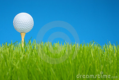 Golf ball on tee in a grass field