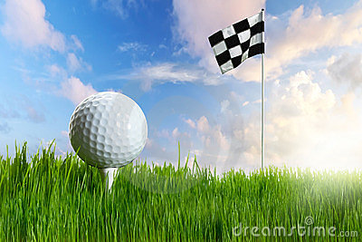 Golf ball on tee in the grass with flag