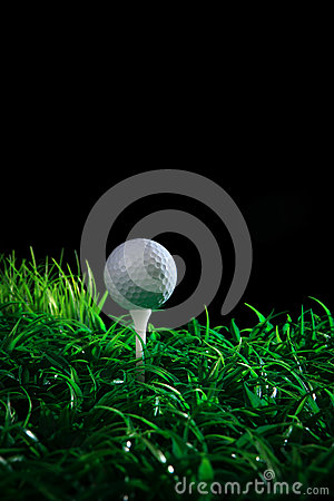 Golf ball and tee in green grass