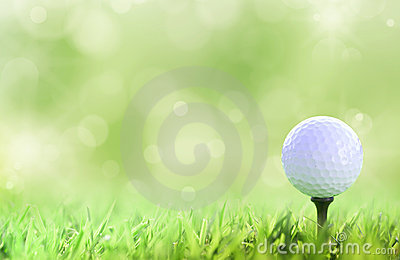 Golf ball on tee over a green