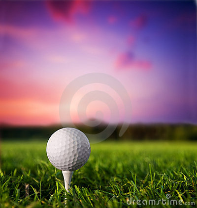 Golf ball on tee at sunset