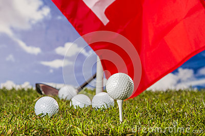 Golf balls, green grass, clouds background