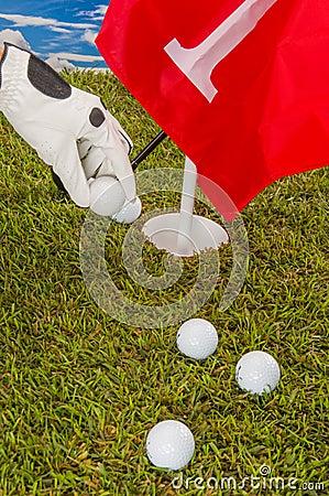 Golf balls, green grass, clouds background