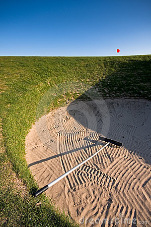 Golf bunker with rake and red flag