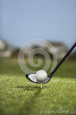 Golf club and golf ball on tee.