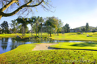 Golf course with green grass, sand bunker and pond