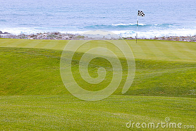 Golf course greens leading to hole by the ocean