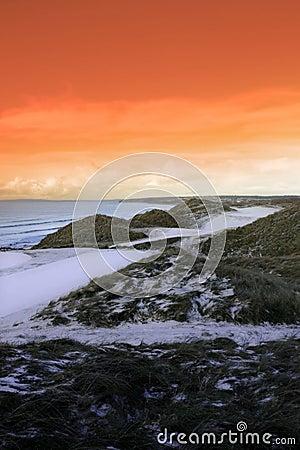 Golf fairway with winter orange sunset sky