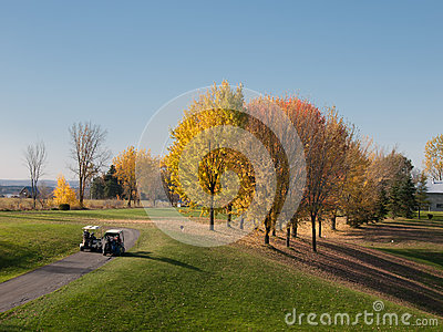 Golf in fall with men driving carts
