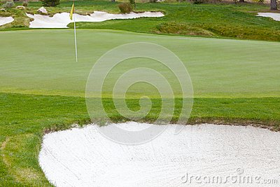 Golf green and flag pin surrounded by sand traps